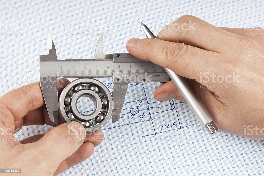 Technical drawing and callipers with bearing in hand royalty-free stock photo