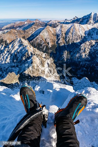 istock Technical mountain boots with crampons on the climber's legs and two ice axes with a beautiful mountain landscape in the background. While resting after hiking on the summit. 1291916136