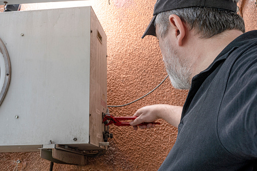 Technical professional in air conditioning adjusting the refrigerant inlets in an external unit of a split air unit.