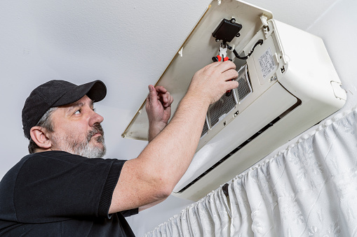 Technical professional in air conditioning changing the wifi command of an internal unit of a split air unit.