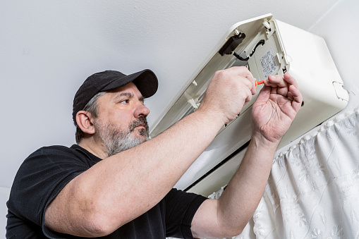 Technical professional in air conditioning finishing assembling the housing of an internal unit of a split air system.