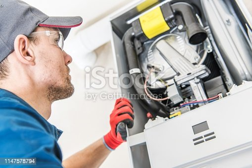 Technician and the Heater Issue. Caucasian Worker Looking Inside Central Gas Heater Trying to Fix the Problem.