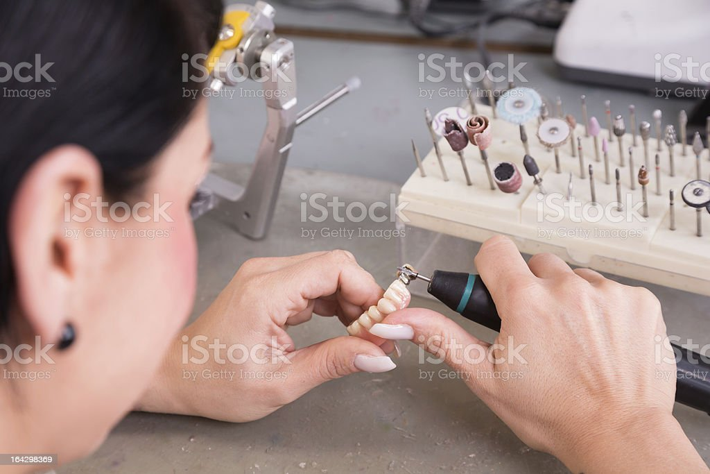 Technician at work in a dental lab or workshop royalty-free stock photo