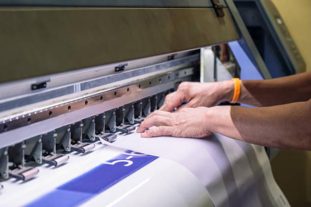 Technician catching a vinyl paper on large inkjet printer stock photo