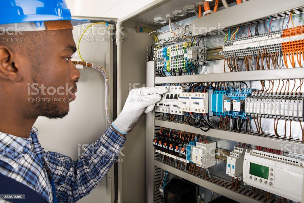 Technician Checking Fusebox stock photo
