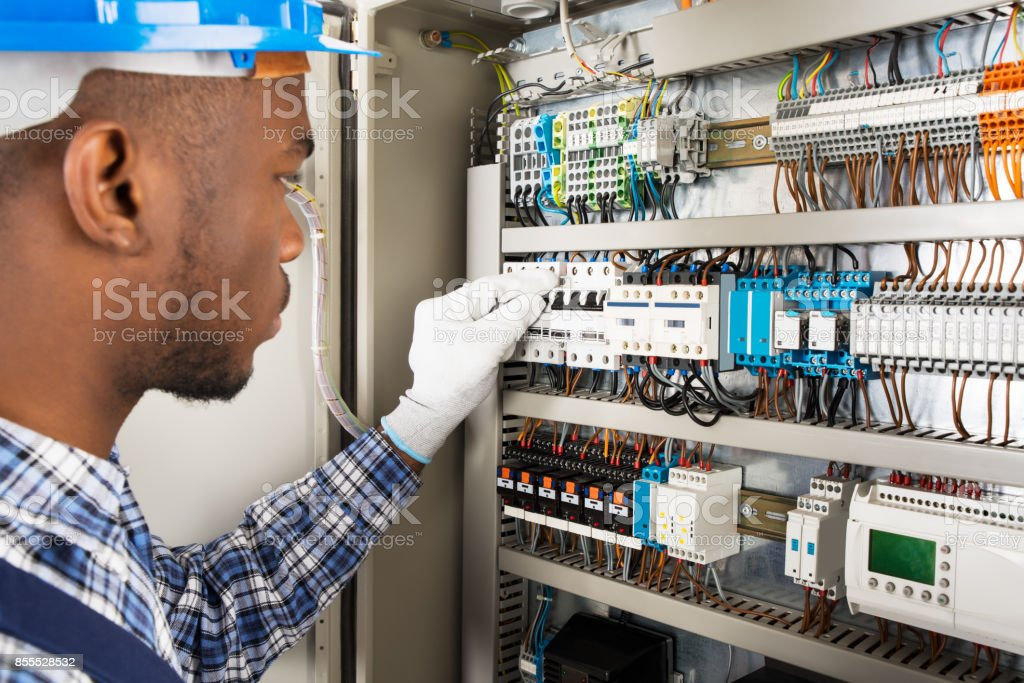Technician Checking Fusebox stock photo