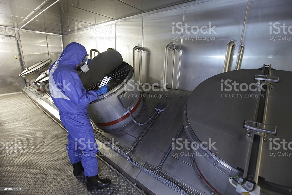 Technician checking technological system with tablet in high tech environment stock photo