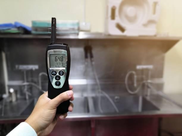 technicus die de temperatuur en vochtigheid in de centrale steriele toevoer afdeling controleert. cleanroom en operatiekamer concept. - luchtvochtigheid stockfoto's en -beelden