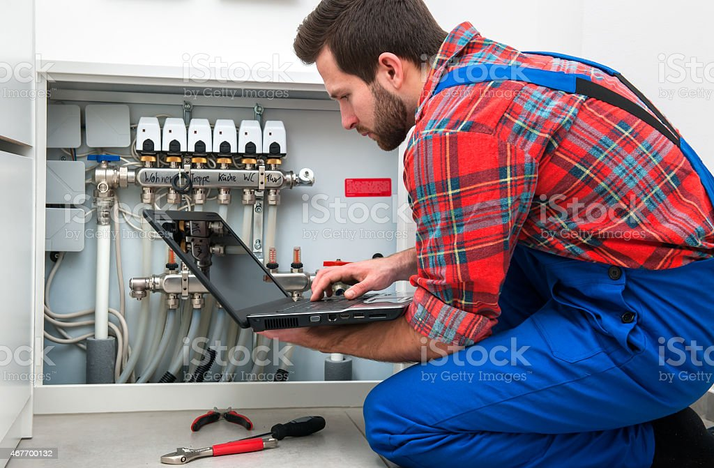Technician checking the pipes' diagnostics at work stock photo