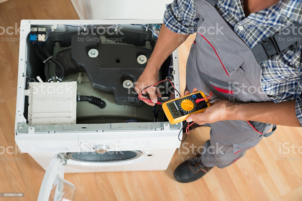 Technician Checking Washing Machine With Digital Multimeter stock photo