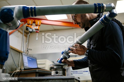Technician checks a metal part with a robotic arm in a workshop