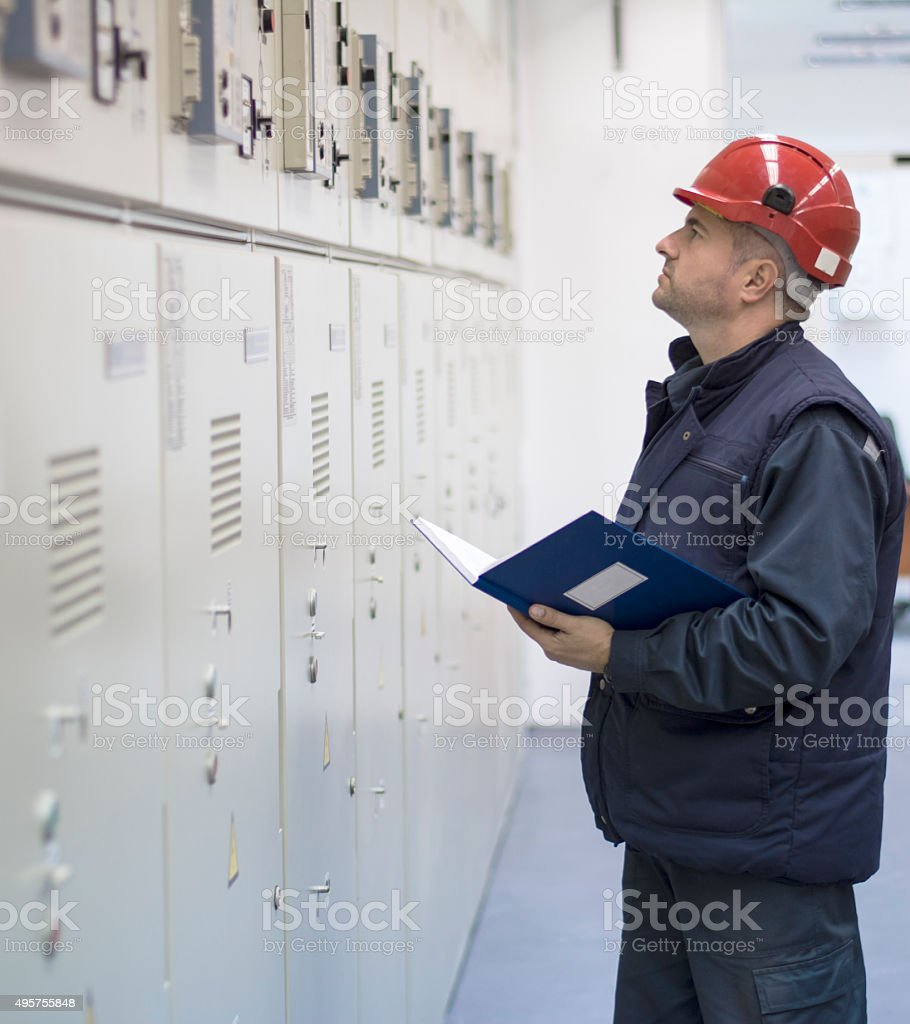 Technician Checks the Functionality of the Equipment in Electrical Room stock photo