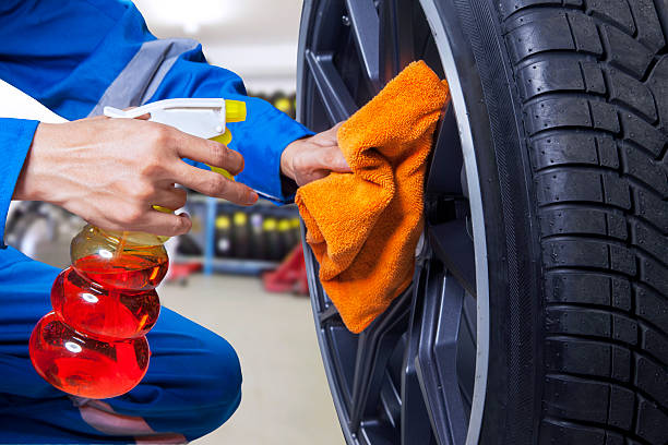 Technician cleaning a tire at workshop stock photo