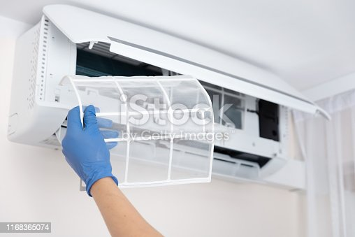 istock Technician cleaning air conditioner filter 1168365074