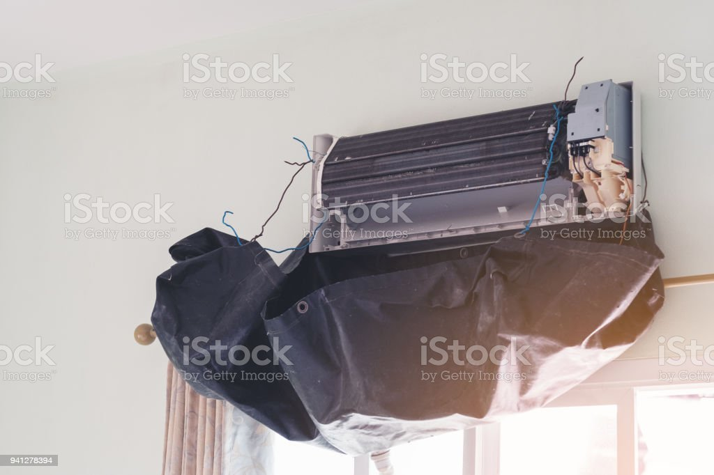 Technician cleaning air conditioner in house. A/C or AC is fixed or maintenance.Electrician cleaning filter of air condition device in a room stock photo