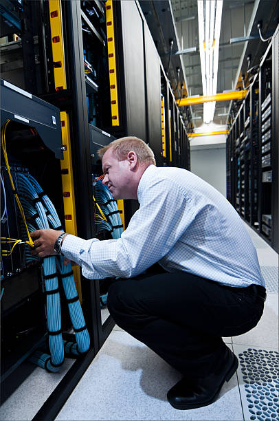 IT technician crouched down, exploring network cables stock photo