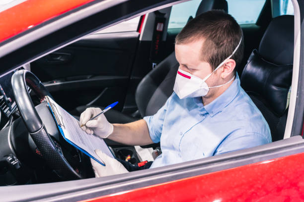 A technician doing a security inspection inside a vehicle protected with a mask and gloves to prevent the spread of virus A young caucasian technician doing a security inspection inside a vehicle protected with a mask and gloves to prevent the spread of virus driver occupation stock pictures, royalty-free photos & images
