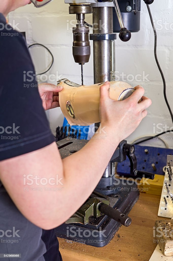 Technician drilling hole into prosthetic limb. – Foto