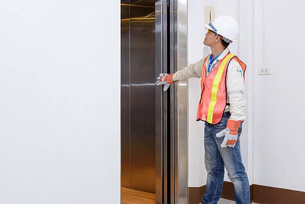 technician - engineer investigate work adjustment mechanism lift - ascensore foto e immagini stock