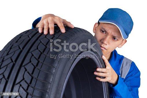 1047558948 istock photo Technician examining a tire 469097830