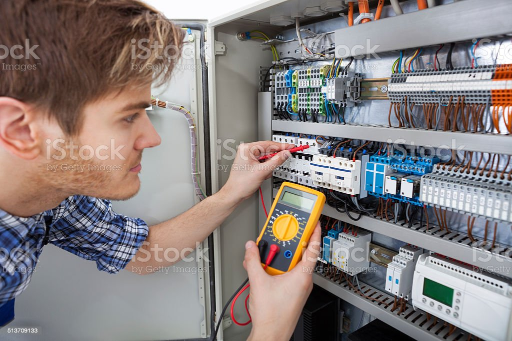 Technician Examining Fusebox With Insulation Resistance Tester stock photo