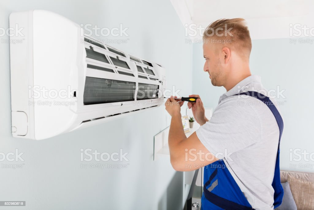 Technician Fixing Air Conditioner stock photo