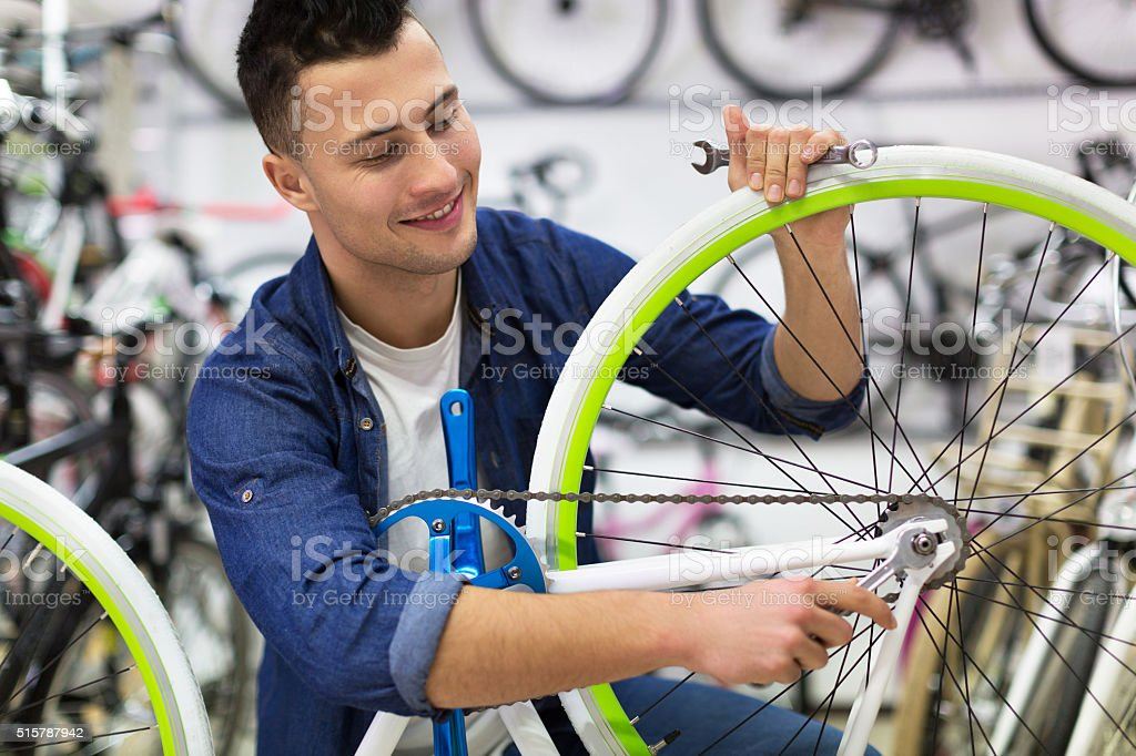 Technician fixing bicycle in repair shop stock photo