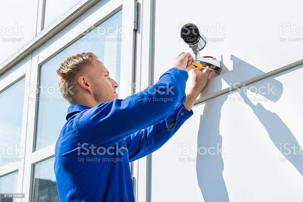 Technician Fixing Camera On Wall stock photo