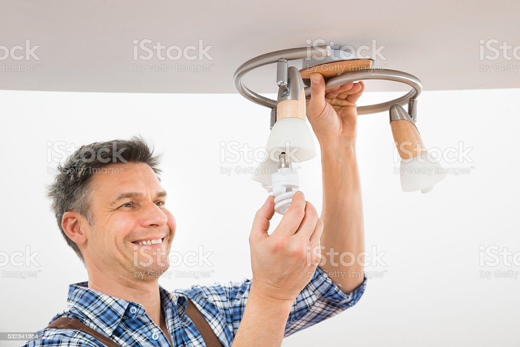 Technician Fixing Light On Ceiling stock photo