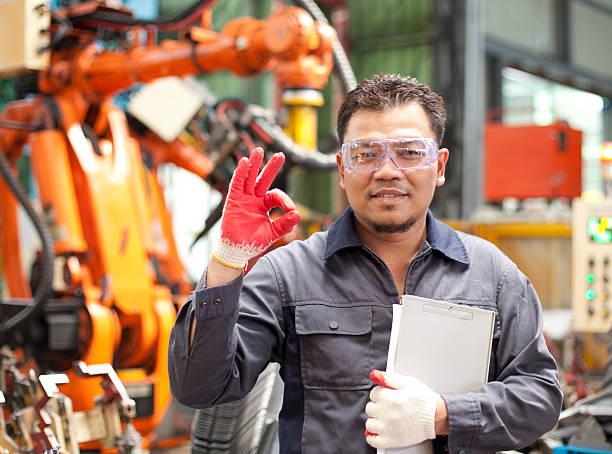 Techniker geben die OK Zeichen in einer Fabrik – Foto