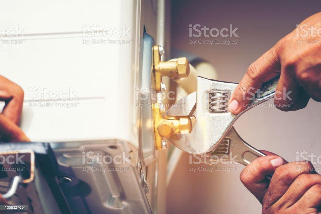 Techniker Hand mit Fix Schraubenschlüssel festziehen Außengerät der Klimaanlage, Mann hält einen Schraubenschlüssel in der Hand. – Foto