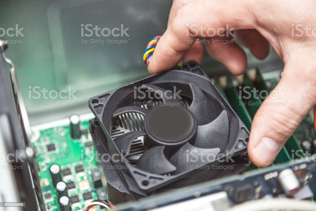 Technician hands installing CPU cooler fan on a computer pc motherboard stock photo