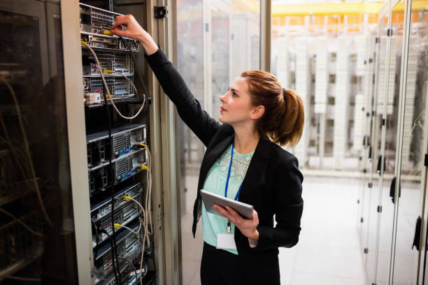 Technician holding digital tablet while examining server stock photo