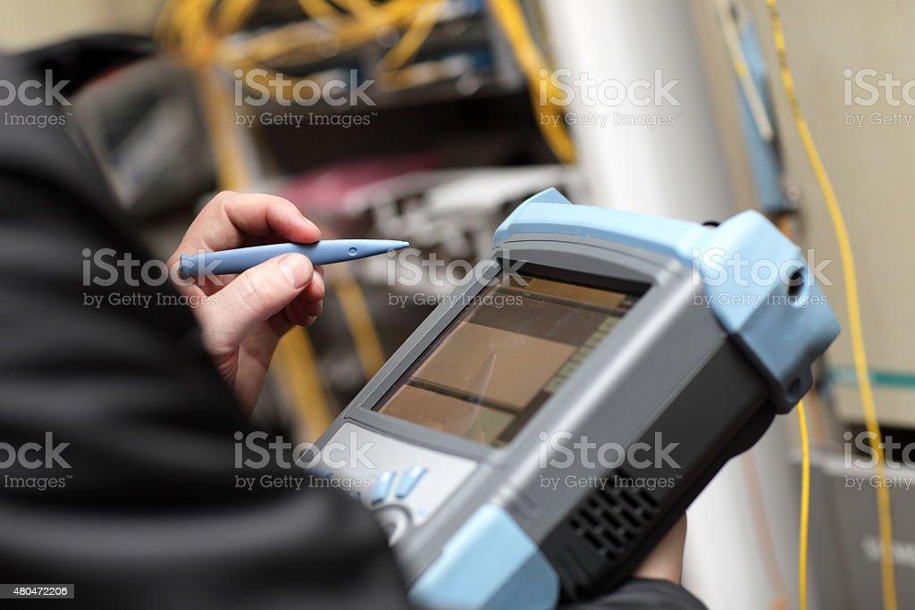 Technician holding reflectometer stock photo