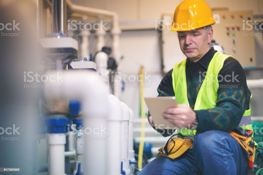 Technician in boiler room using tablet pc stock photo