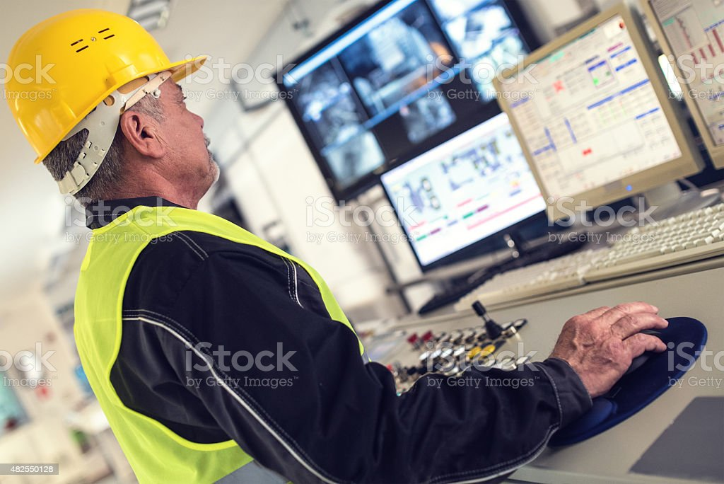 Technician in control room Senior Technician Working at Computer Station. 2015 Stock Photo