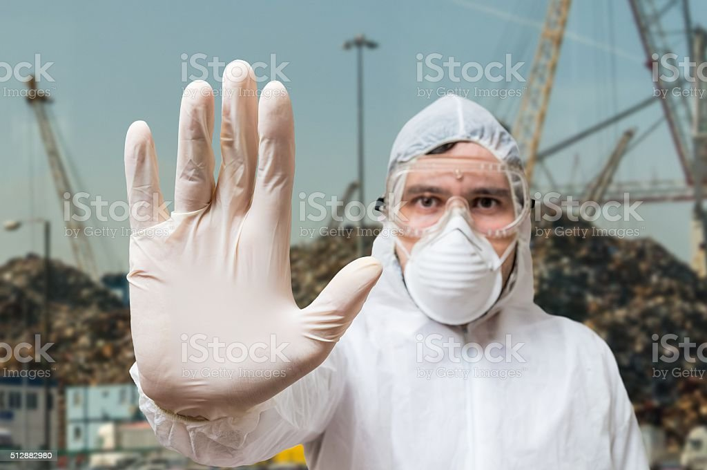 Technician in coverall showing hand as stop gesture. stock photo