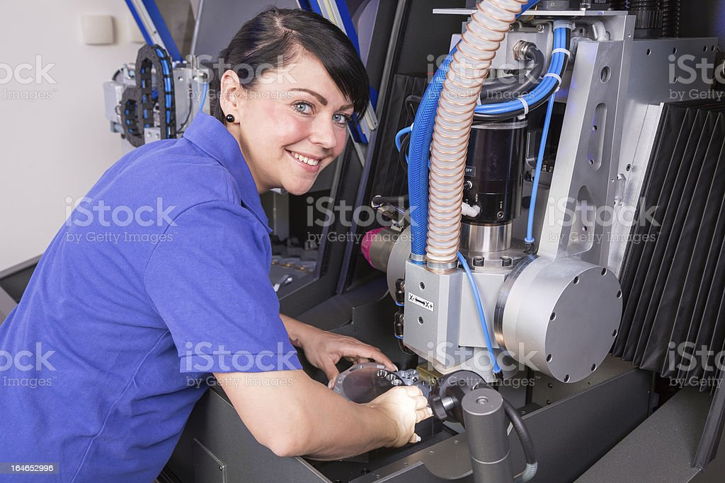 Technician in dental lab working at drilling machine stock photo