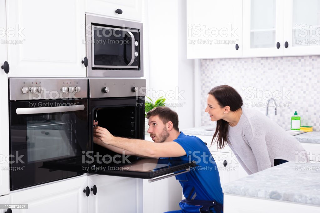 Technician In Overall Fixing Oven In Kitchen Smiling Young Woman Looking At Technician Fixing Oven In Kitchen Adult Stock Photo