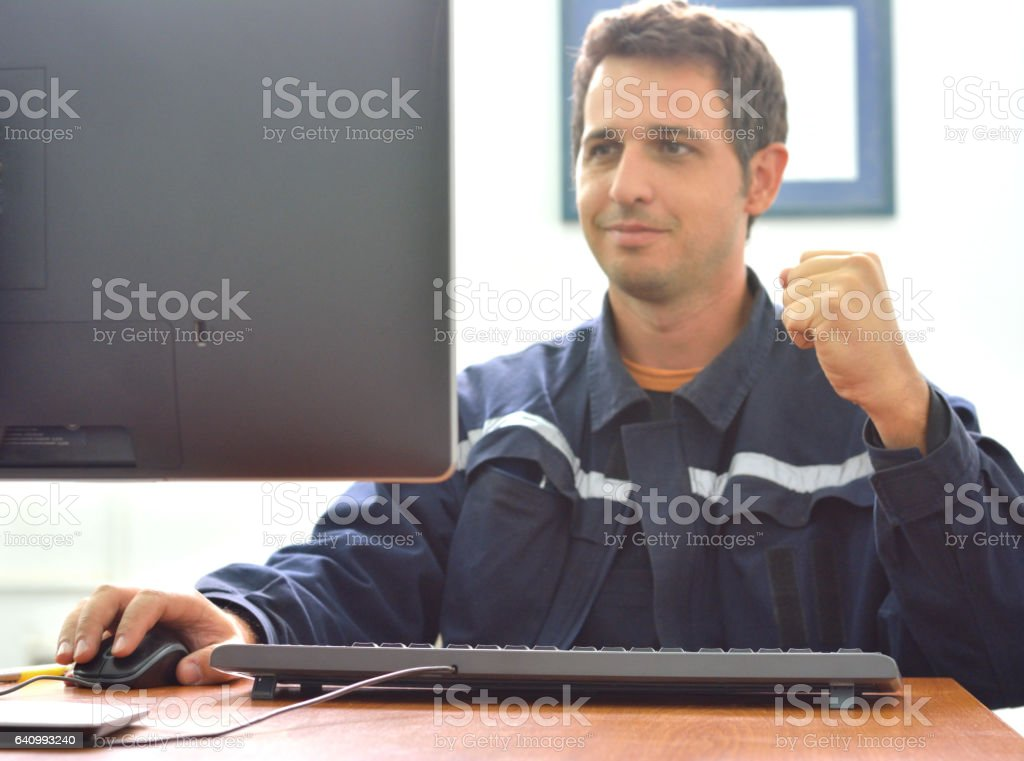 Engineer doing victory sign in office when he works on computer.