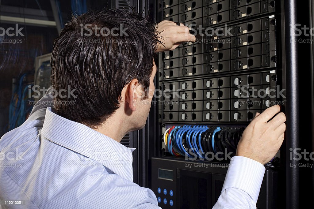 IT Technician in Server Room Working on Network Equipment royalty-free stock photo