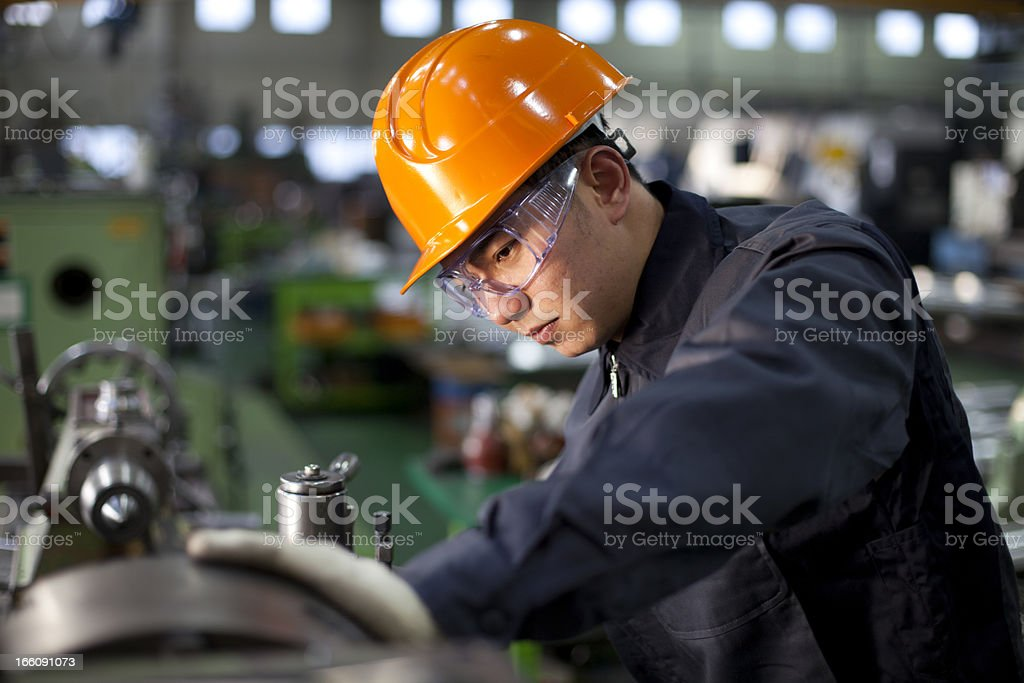 Technician in uniform and hard hat working on a machinery stock photo