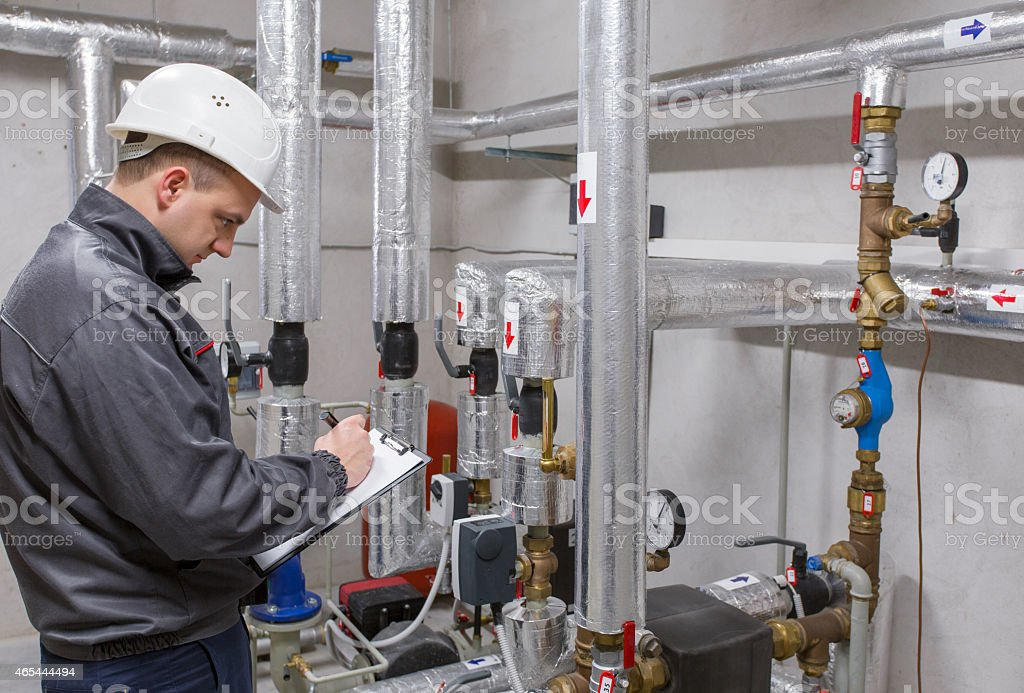 Technician inspecting heating system stock photo