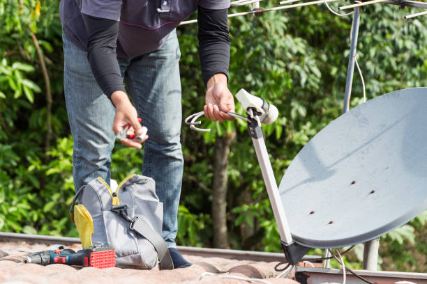 Technician installing satellite dish and television antenna on roof top Skillful technician worker installing satellite dish and television antenna on roof top antenna aerial stock pictures, royalty-free photos & images