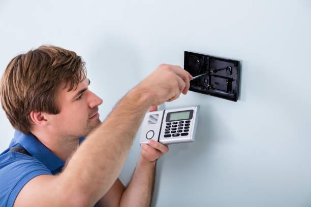 Techniker installieren Sicherheitssystem mit Schraubendreher – Foto