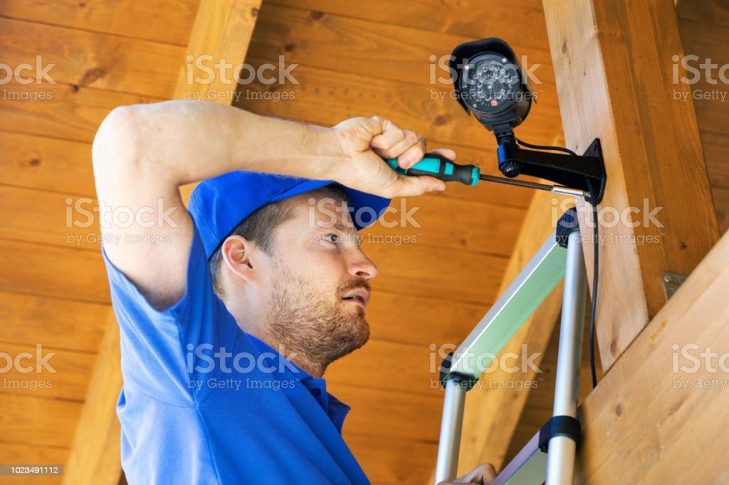 technician installing surveillance camera in the house carport stock photo