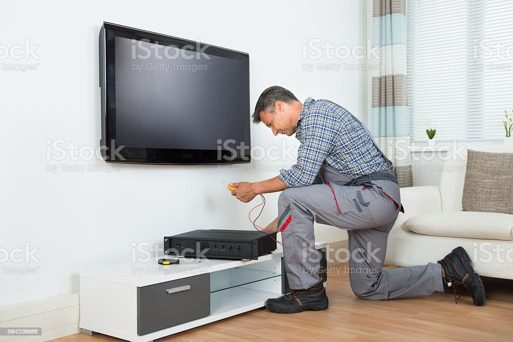 Technician Installing TV Set Top Box At Home stock photo