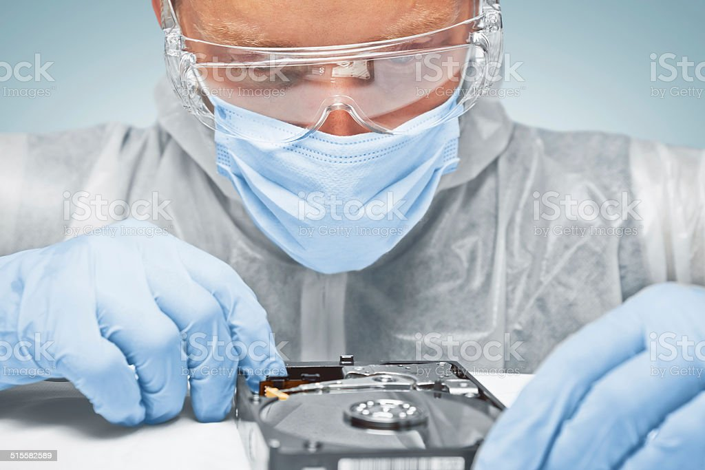 Technician is analyzing the hard disk stock photo