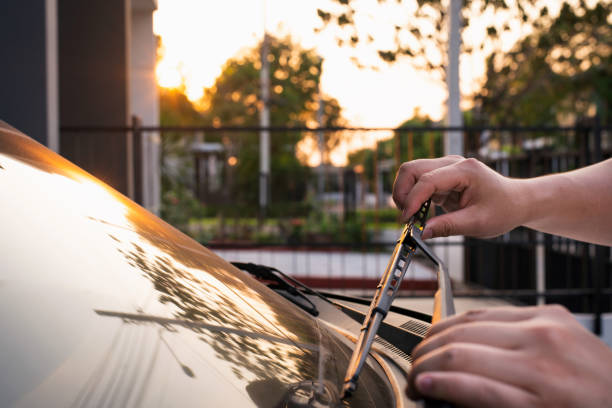 Technician is changing windscreen wipers on a car station Technician is changing windscreen wipers on a car station,man hand picking up windscreen wiper or Mechanic check old wiper blade on sedan car. windshield wiper stock pictures, royalty-free photos & images