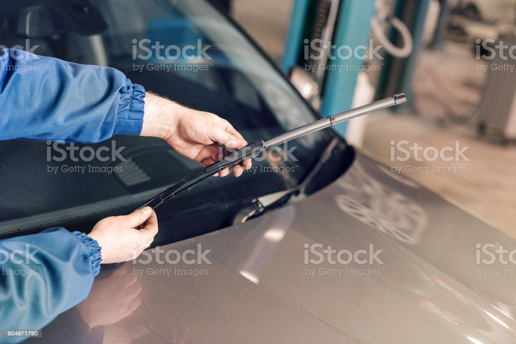 Techniker ist Scheibenwischer auf einer Auto-Station ändern. – Foto